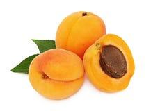 Gehele twee en een halve abrikoos met (geïsoleerde) bladeren Royalty-vrije Stock Afbeeldingen