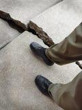 Gehen auf defekten gefährlichen Bürgersteig Stockbild