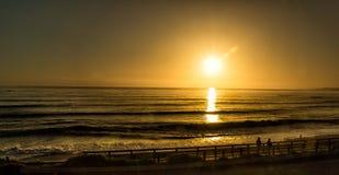 Gehen auf einen Strand bei Sonnenuntergang lizenzfreie stockfotografie