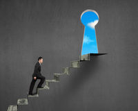 Gehen auf Geldtreppe zum Schlüsselloch Stockfoto