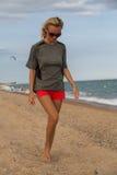 Gehen der jungen Frau entspannt entlang dem Strand Stockfoto