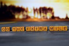 Gehen die Extrameile auf Holzklötzen Kreuz verarbeitetes Bild mit bokeh Hintergrund lizenzfreies stockbild
