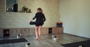 Gehen durch die junge Frau des Yogastudios wird sie kommend zu ihrer Yogameditationsklasse fertig ihren, Sport zu setzen zu begin stock footage
