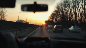 Gehen in ein Auto hinunter die Straße bei Sonnenaufgang stock video footage