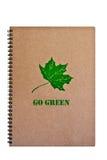 Gehen Grün auf braunem Notizbuch mit grünem Blatt. Stockbilder