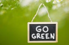 Gehen Grüne geschrieben auf Tafel auf grünem Wiesenhintergrund Stockfoto