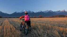 Gehen kaukasische Kinder eins mit Fahrrad auf dem Weizengebiet Kleines Mädchen, das schwarzen orange Zyklus auf Hintergrund von s stockfoto