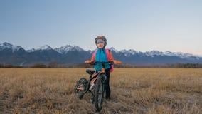 Gehen kaukasische Kinder eins mit Fahrrad auf dem Weizengebiet Kleines Mädchen, das schwarzen orange Zyklus auf Hintergrund von s lizenzfreie stockfotos