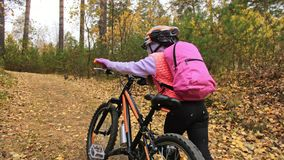 Gehen kaukasische Kinder eins mit Fahrrad im Herbstpark Das kleine Mädchen, das schwarzen orange Zyklus im Waldkind geht, geht zu stock video footage