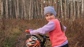 Gehen kaukasische Kinder eins mit Fahrrad im Herbstpark Das kleine Mädchen, das schwarzen orange Zyklus im Waldkind geht, geht zu stock video