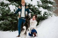 Gehen Männer und ein Mädchen in den Winterwald mit einem Hund Lizenzfreie Stockfotos