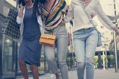 Gehen mit drei jungen Mädchen glücklich mit Einkaufstaschen Stockfotos