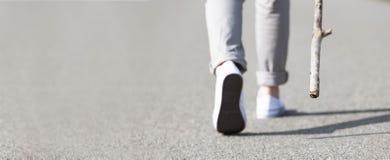 Gehen mit Turnschuhen auf Straße lizenzfreie stockbilder