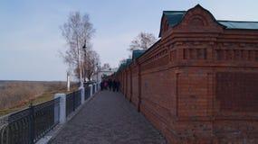 Gehen nahe dem hohen Zaun des roten Backsteins Stockbild