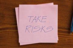 Gehen Sie das Risiko ein, das auf eine Anmerkung geschrieben wird Stockfotografie