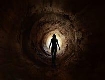 Gehen Sie in die Leuchte im dunklen Tunnel