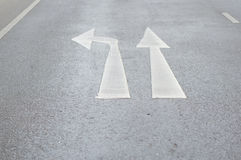 Gehen Sie gerade oder biegen Sie Verkehrszeichen auf gepflasterter Straße nach links ab Lizenzfreies Stockfoto
