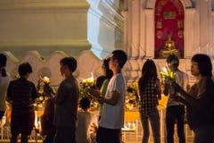 Gehen Sie mit beleuchteten Kerzen in der Hand um einen Tempel Lizenzfreie Stockfotos