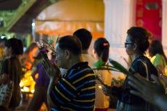 Gehen Sie mit beleuchteten Kerzen in der Hand um einen Tempel Stockfoto