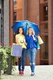 Gehen von zwei schönen Freundinnen in voller Länge mit einem Regenschirm und Einkaufstaschen Stockbild