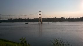Gehende Brücke über einem Fluss bei Sonnenuntergang Lizenzfreie Stockfotografie