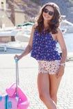 Gehende Ferien des Mädchens mit rosa Koffer Stockfoto