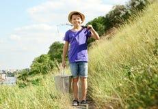 Gehende Fischerei des netten Jungen am Sommertag Stockfoto