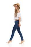 Gehende Frau in den Jeans, in den hohen Absätzen und in Straw Hat Stockfotos