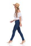 Gehende Frau in den Jeans, in den hohen Absätzen und in Straw Hat Profile Lizenzfreies Stockbild