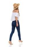 Gehende Frau in den Jeans, in den hohen Absätzen und in Straw Hat Rear View Stockfotografie