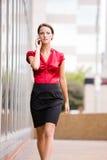 Gehende Geschäftsfrau bei der Unterhaltung an ihrem Telefon Lizenzfreies Stockfoto