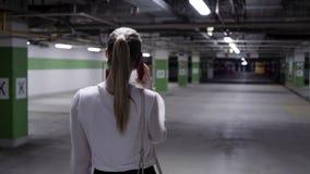Gehende junge Frau mit dem Pferdeschwanz, weißem Hemd und schwarzem Rock in der Garage stock video