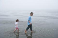 Gehende Kinder bei Ebbe, nebeliger Tag Stockbilder