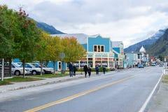 Gehende Leute und Autofahren durch die Geschäfte auf Main Street in Skagway Alaska lizenzfreie stockbilder