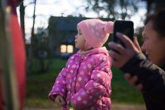 Gehende Mädchen mit ihrer Tochter in der Abendstadt und Unterhaltung auf der Videokommunikation mit ihrem Vater lizenzfreies stockfoto