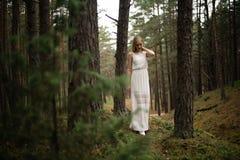 Gehende sch?ne junge Blondinewaldnymphe im wei?en Kleid im immergr?nen Holz lizenzfreies stockfoto