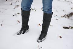 Gehende Stiefel der jungen Frau im Schnee Lizenzfreie Stockbilder