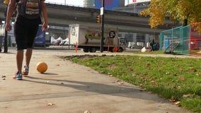 Gehende Straße des Jungen, die Fußball tritt stock video footage