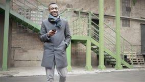 Gehender afroer-amerikanisch Mann, der am Telefon spricht H?bscher Afroamerikanerkerl in einem Mantel und in einem Schal, die am  stock video footage