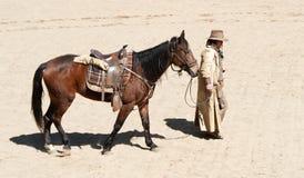 Gehender Cowboy sein Pferd Stockfotos