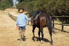 Gehender Cowboy sein Pferd Lizenzfreies Stockfoto