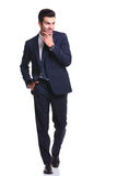 Gehender Geschäftsmann beim Halten von einer Hand zu seinem Kinn Lizenzfreies Stockfoto