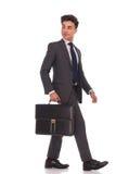 Gehender Geschäftsmann, der zurück über seiner Schulter beim Halten schaut Lizenzfreies Stockfoto