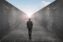 Gehender Geschäftsmann eine Weisenstraße in Richtung zur Ausgangssonnen-Himmelansicht Lizenzfreie Stockfotografie