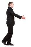 Gehender Geschäftsmann im schwarzen Anzug ist gehender Händedruck. Stockbilder