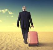 Gehender Geschäftsmann mit Koffer in einer Wüste Stockfoto