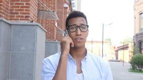 Gehender junger schwarzer Mann, der auf Mobile, Front View Outdoor spricht stock video