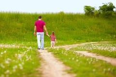 Gehender ländlicher Fußweg des Vaters und des Sohns Stockfotos