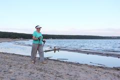 Gehender Nordic - ältere Frau wandert entlang dem Fluss Lizenzfreies Stockbild