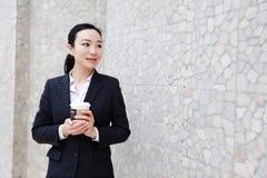 Gehender trinkender Kaffee der Geschäftsfrau lizenzfreie stockbilder